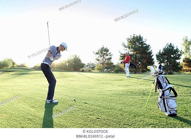 Friend watching man hitting ball on golf course