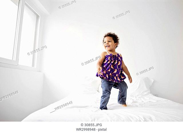 Young girl with curly black hair jumping on a bed, wearing jeans and printed top, smiling
