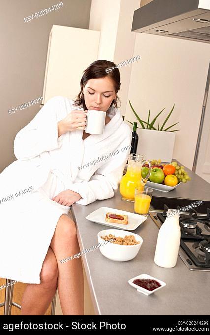 Young woman enjoying coffee in kitchen