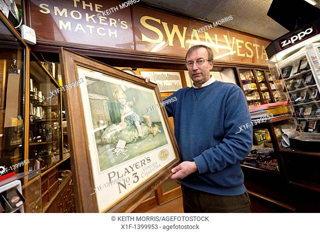 Peter Lloyd - the owner of A E Lloyd and Son Tobacconists, established 1890, Aberystwyth Wales UK, holding an old advert for Players No3 Cigarettes