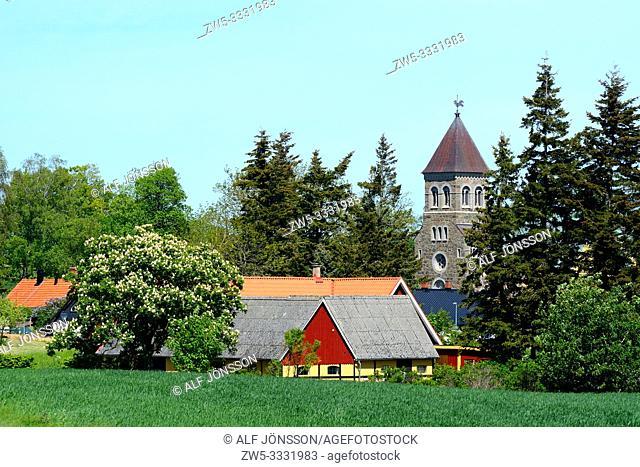 Swedish farm and a church among trees in Bjäresjö, Scania, Sweden