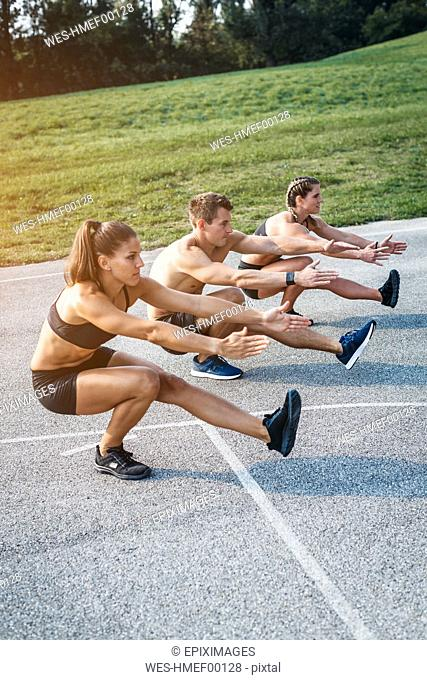 Sporty team during workout, standing on one leg, balance training