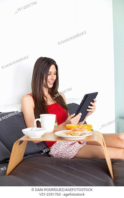 Pretty brunette woman using digital tablet and having breakfast in bed