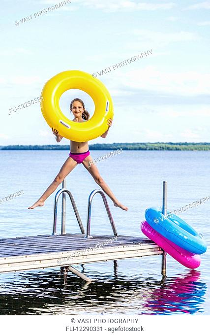 Girl jumping on dock by Balsam Lake holding a yellow inflatable ring; Ontario, Canada
