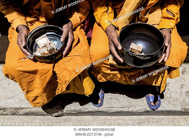 Close up of monks collecting alms, Leh, Ladakh, India