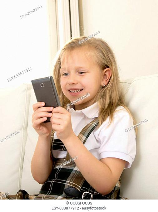 sweet cute and beautiful 6 or 7 years old female child with blond hair in school uniform sitting on home sofa couch using internet app on mobile phone playing...