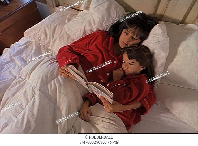 mother and daughter in red pygamas laying in white bed reading together