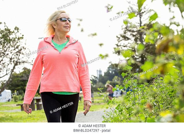 Older Caucasian woman walking in park