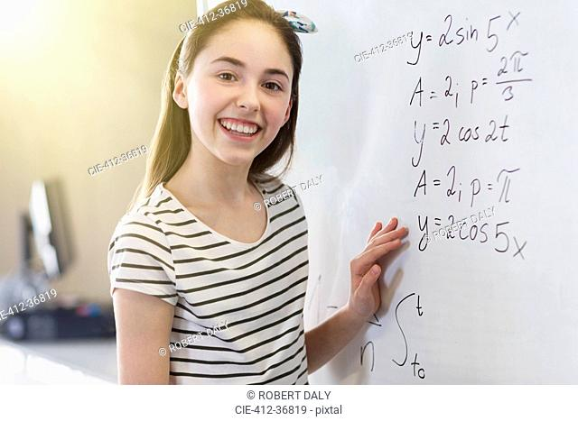 Portrait smiling, confident girl student solving physics equation at whiteboard in classroom