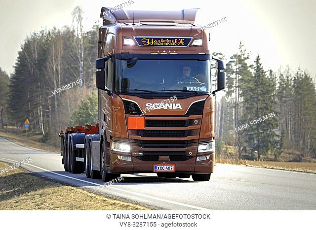 Salo, Finland - April 5, 2019: Bronze Next Generation Scania R580 truck of AH Trans Oy for chemical container transport on road, high beams briefly on