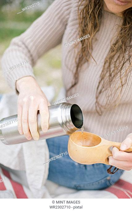A woman pouring a drink from a flask into a cup