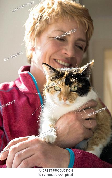 Close-up of mature woman with cat in her arms, Bavaria, Germany