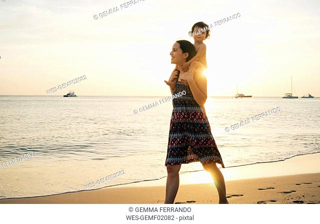 Thailand, Krabi, Koh Lanta, Mother with little daughter on her shoulders on the beach at sunset