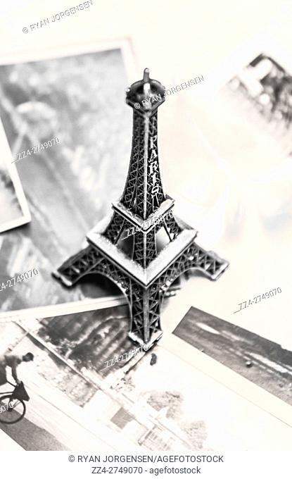 Little silver souvenir Eiffel tower on background of black and white photos. Nostalgia in France