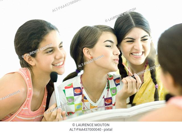 Three young female friends putting on make-up