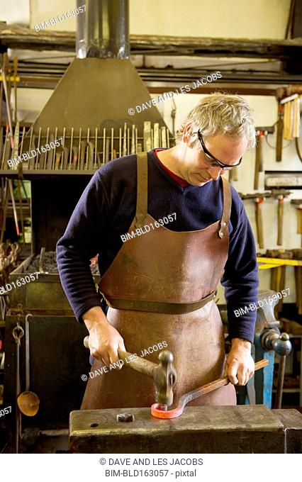 Caucasian blacksmith hammering metal in shop