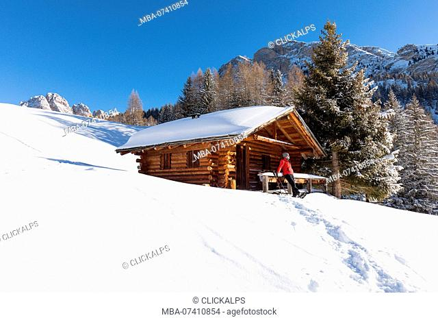 a hiker is relaxing on the snow in front of a mountain hut in Val Gardena, Bolzano province, South Tyrol, Trentino Alto Adige, Italy