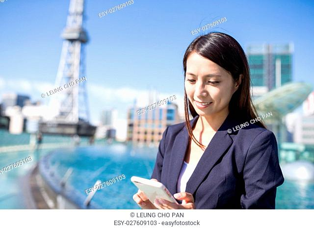 Business woman using mobile phone in Nagoya city