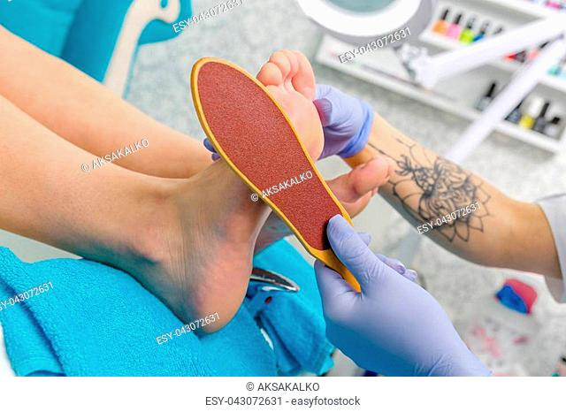 Pedicure master during work. Closeup of female feet and hands in gloves with a nail file
