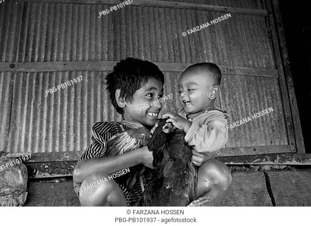 A child holding a hen and his younger brother aftermath of a devastating cyclone The cyclone Aila swept over the coastal areas of Bangladesh on May 25