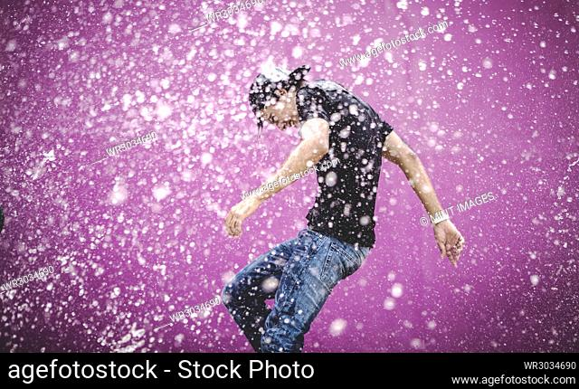Young man standing in a shower of water drops