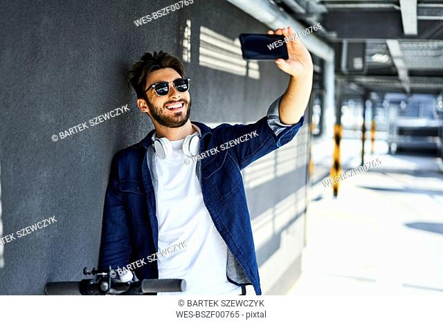Portrait of smiling man taking selfie with smartphone