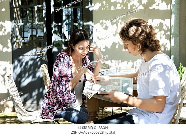 Young couple discussing news in newspaper