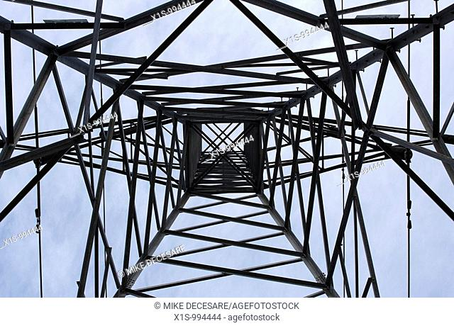 Looking up into the center of a very large, metal high voltage power line tower in Washington