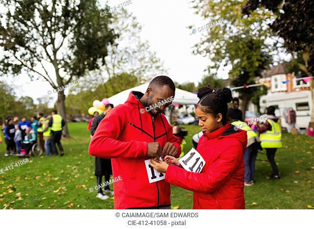 Daughter pinning marathon bib on father runner at charity run in park