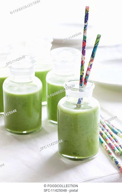 Cold pea soup in bottles with straws