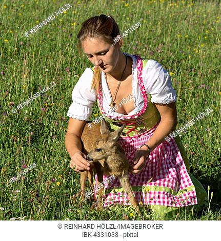 Woman in dirndl with a tame fawn in a flower meadow, Tyrol, Austria