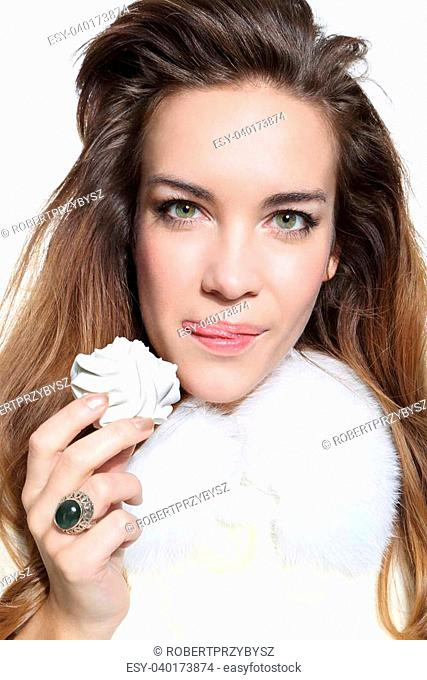 Beautiful fashion model in white fur with meringue