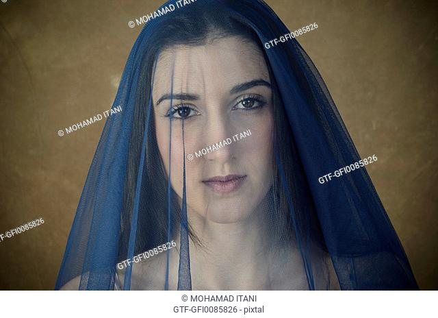 Beautiful young woman covered with blue chiffon scarf