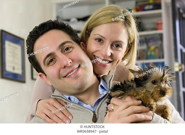 Portrait of a Hispanic man and a woman with a Yorkshire terrier
