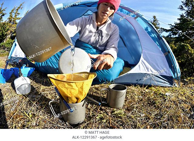 Woman backpacker prepares coffee at camp near Upper Fuller Lake in the Kenai National Wildlife Refuge on the Kenai Peninsula in South-central Alaska