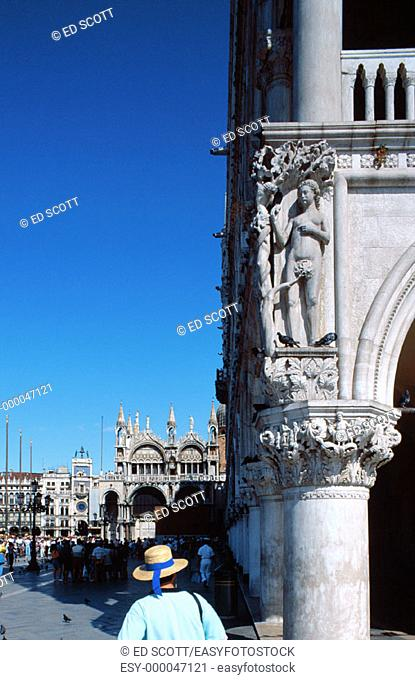 The Doges Palace corner and gondolier wearing a straw hat. Venice. Italy