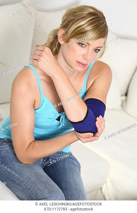 woman checking her elbow wearing bandage