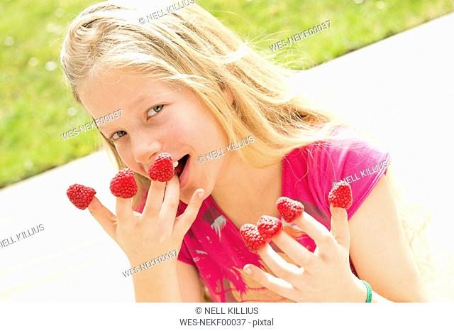 Portrait of smiling girl with raspberries on fingers