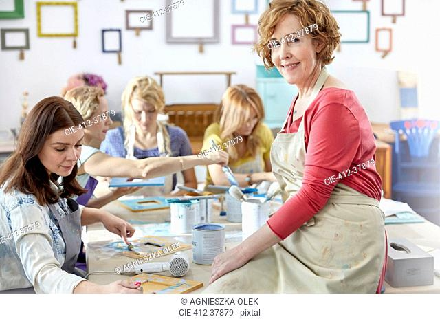 Portrait confident, smiling female art instructor helping students painting in art class workshop
