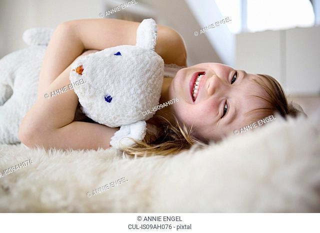 Girl lying on furry bed cuddling teddy bear