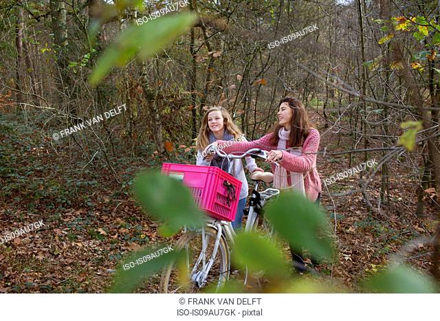 Teenage girls walking in forest pushing bicycle with pink crate attached
