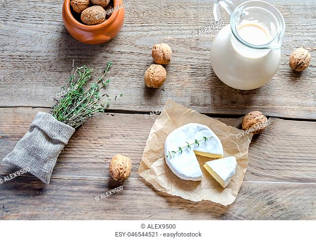 Camembert with pitcher of milk and whole nuts