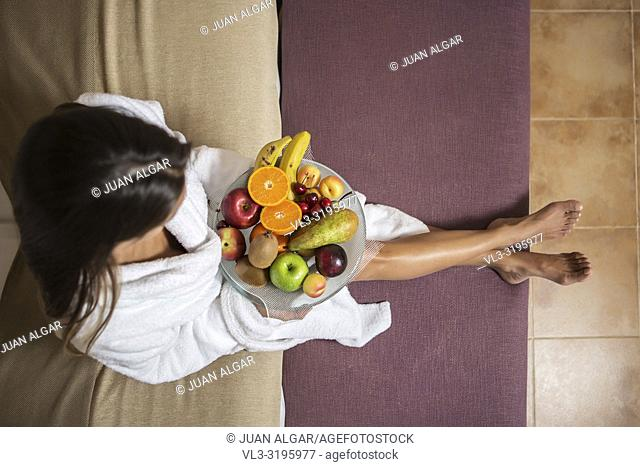 From above shot of woman in white bathrobe sitting on bed with plate of colorful fruit