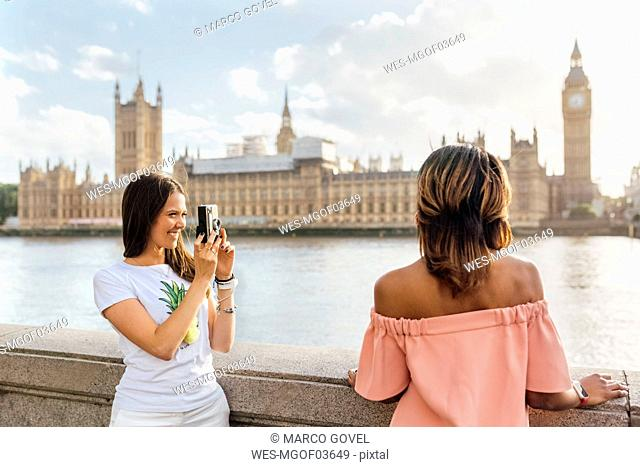 UK, London, woman with friend taking a picture near Palace of Westminster