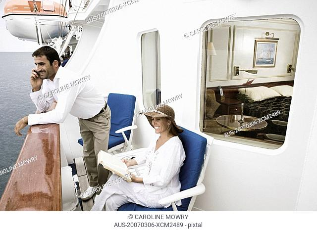 Mid adult man talking on a mobile phone with a mid adult woman sitting on a chair and smiling