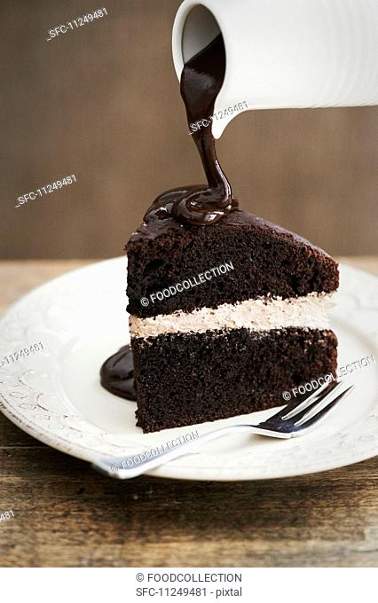 A slice of chocolate cake with a cream filling and chocolate sauce