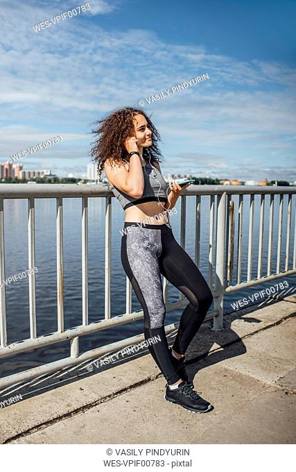 Smiling young athletic woman with smartphone and earbuds at the riverside