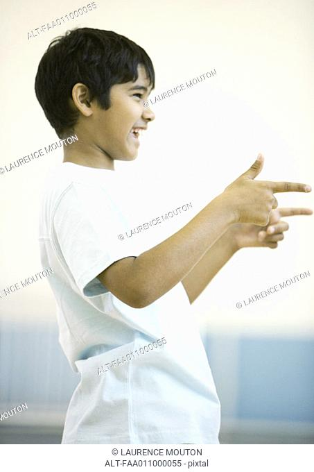 Teen boy pointing with both hands, smiling