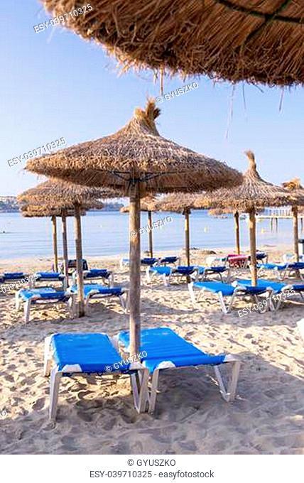 Beautiful Sandy Beach with Straw Umbrellas at Sunrise in Paguera, Majorca ( Balearic Islands - Spain )
