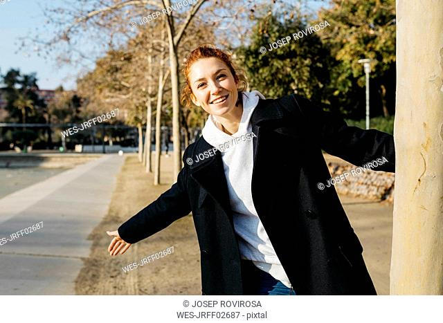 Portrait of happy redheaded young woman in a city park